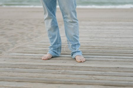 close-up photo of man legs standing on wood way in beach