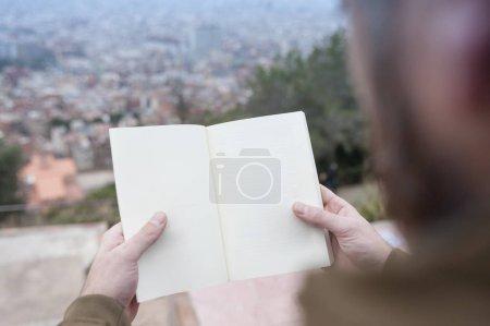 Photo pour Mains masculines tenant livre ouvert vide avec vue sur la ville floue de Barcelone en arrière-plan - image libre de droit
