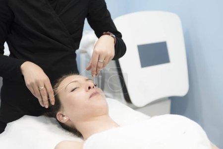 Photo pour Esthéticienne, épilation du visage avec enfilage en salle lumineuse - image libre de droit