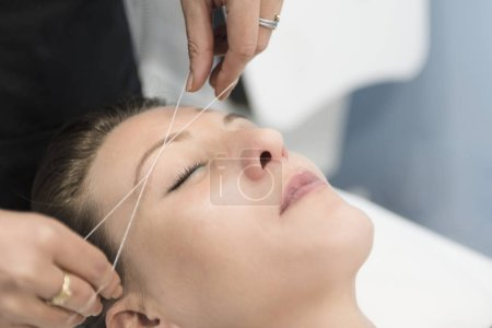 Cosmetologist removing facial hair with Threading...