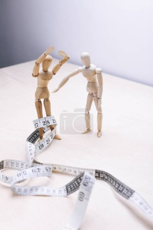 wooden mannequins couple with measure tape. nutritional concept