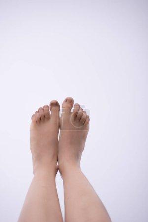 Primer plano de las piernas femeninas levantadas sobre fondo blanco
