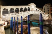 VENICE, ITALY - AUGUST 12, 2017: Rialto Bridge and Grand Canal with people and tourists at night in Venice, Italy