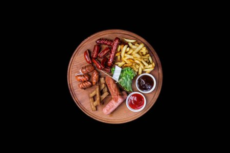 Photo for Beer snacks set. Grilled sausages and french fries served with tomato and BBQ sauce on the cutting board, isolated on a black background. Top view. - Royalty Free Image