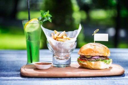 Photo for Perfect meat burger with french fries and fresh cold lemonade. On the cutting board, wooden and green summer background. - Royalty Free Image