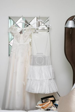 Photo pour Womens white dress with patterns in the shape of flowers hanging on a hanger,womens ballet flats on the coffee table. - image libre de droit