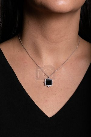 Photo pour Silver chain with a pendant in the shape of a square, in the middle of which a black stone with a rim of diamonds hanging on the neck. - image libre de droit