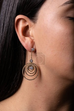 Photo pour Golden womens stud earring with multiple circles hanging on her, dressed to the ear - image libre de droit