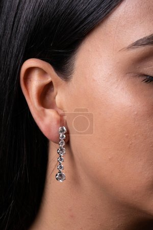 Photo pour Womens silver earring with stones in the middle, dressed to the ear. - image libre de droit