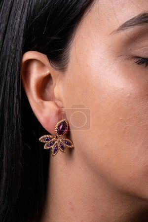 Photo pour Womens rose gold earring with purple stones in the middle, im the shape of leaves dressed to the ear - image libre de droit
