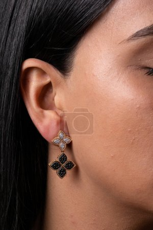 Photo pour Womens gold earring with black and white stones in the shape of two flowers dressed to the ear - image libre de droit