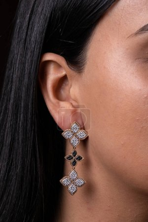 Photo pour Womens gold earring with black and white stones in the shape of three flowers dressed to the ear - image libre de droit