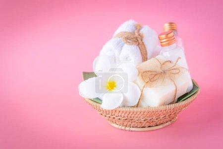 Photo pour Spa bouteille de lait liquide et savon, belle fleur de plumeria, serviettes blanches dans un plateau en bois sur fond rose - image libre de droit