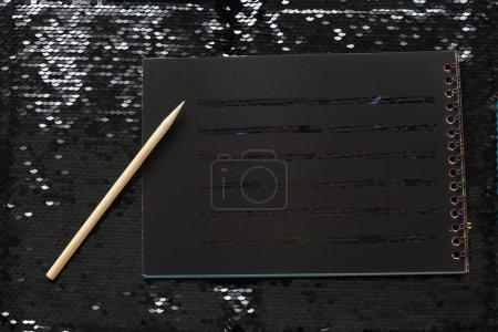 Un cuaderno con hojas negras vacías y un rascador de madera están sobre un brillante fondo brillante de lentejuelas negras, un lugar para escribir notas, escribir un texto recordatorio en papel negro