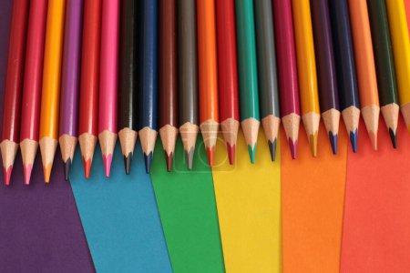 conjunto de lápices brillantes para la creatividad en el fondo de hojas de papel multicolor