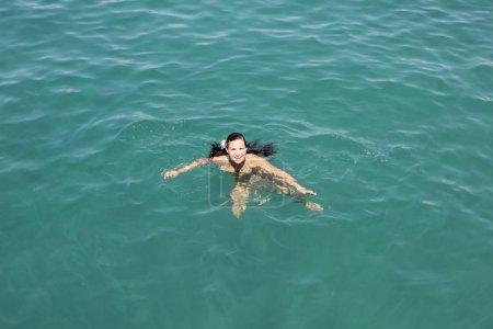 Photo pour Marmaris / Turquie - 13 septembre 2019: Fille heureuse et chérie nage dans la mer avec de longs cheveux qui coulent - image libre de droit