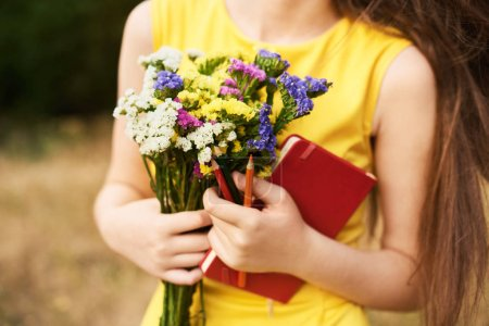 Photo for Long-haired blond girl standing in the park with flowers, a notebook and pencils in her hands. Ready to school. Back to school - Royalty Free Image