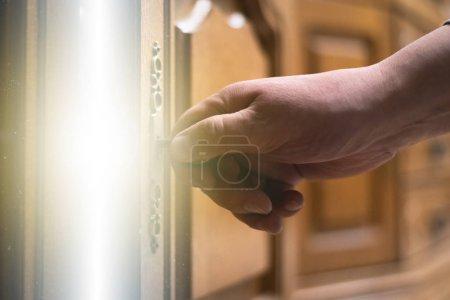 Photo pour L'homme a ouvrir une porte avec un derrière de lumière magique par une clé antique. - image libre de droit