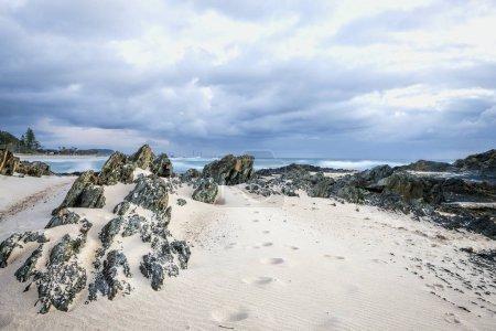 Footprints on sand of rocky beach under blue cloudy sky