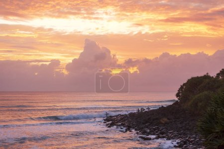 Colourful sunrise with surfers standing on rocks at Burleigh Heads, Gold Coast Australia Australia