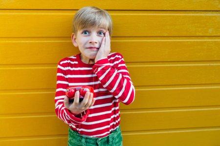 Photo pour Portrait émotif d'un jeune garçon portant une chemise rouge avec une bande blanche tenant un réveil rouge sur fond jaune, à l'extérieur. - image libre de droit