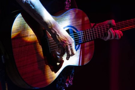 Detail of an acoustic guitar played by a man on the stage illuminated by show lights, horizontal image