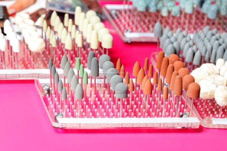 Medizinische Instrumente, Nagelschneider, Schleif- und Poliersteine in verschiedenen Formen und Größen mit Schleifkorn für die Maniküre. Farbcodierung. Rosa Hintergrund, Kopierraum.