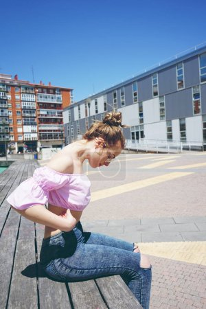 photo of young cute woman in pink shirt and glasses outdoor in summer day