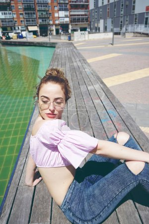 photo of young cute woman in pink shirt and glasses outdoor in summer day with closed eyes