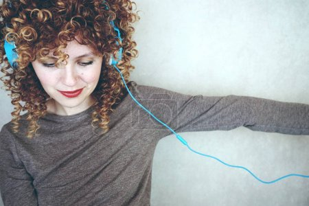 photo of young cute woman with curly hair and blue headphones on grey wall background