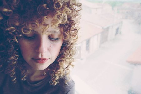 photo of young cute woman with curly hair on grey wall background