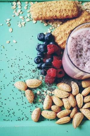 close-up photo of fresh squeeze juice with berries and almond nuts on green table with cookies