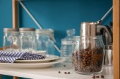 Glass jar with coffee beans on shelf of storage unit indoors