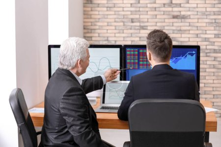 Male brokers working in office. Finance trading concept