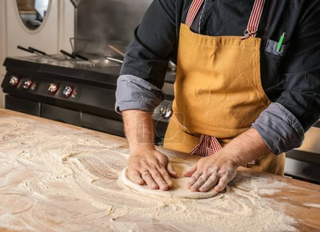 Photo for Male chef preparing dough for pizza in restaurant kitchen - Royalty Free Image