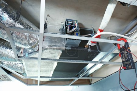 Photo pour Climatiseur industriel et multimètre suspendus sur poutre de plafond à l'intérieur - image libre de droit