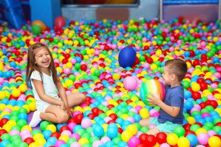 Foto de Lindos niños jugando entre bolas de plástico - Imagen libre de derechos