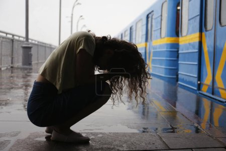 Depressed young woman at railway station on rainy day