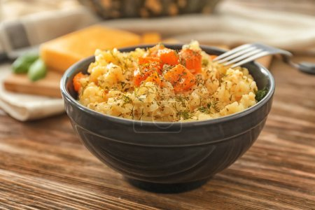 Bowl with delicious pumpkin risotto on wooden table