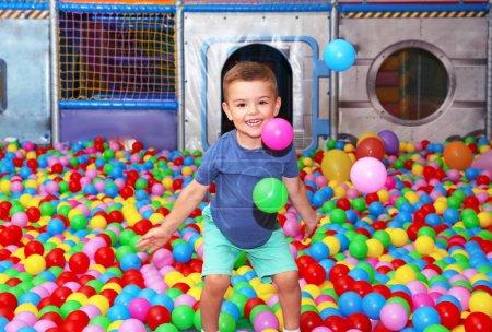 Foto de Lindo niño jugando entre bolas de plástico - Imagen libre de derechos