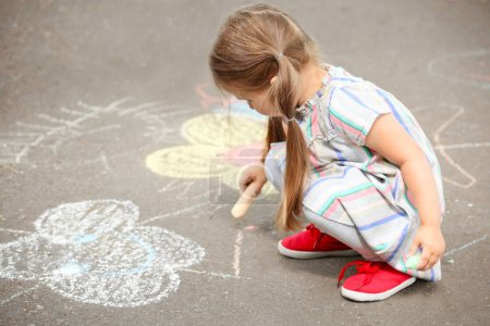 Cute little girl drawing with chalk on  asphalt