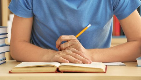 Teenager boy doing homework in library, closeup