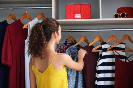 Teenage girl choosing clothes in wardrobe at home