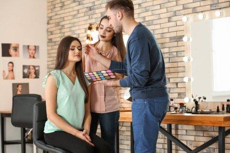 Professional makeup artist teaching trainee in salon. Apprenticeship concept