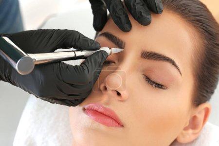 Photo pour Jeune femme subissant une procédure de maquillage permanent des sourcils dans un salon de beauté - image libre de droit