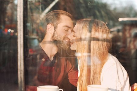 Young romantic couple in cafe, view from outdoors through window