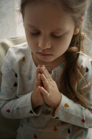 Religious Christian girl praying indoors