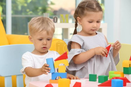 Photo for Cute children playing with constructor on table at home - Royalty Free Image