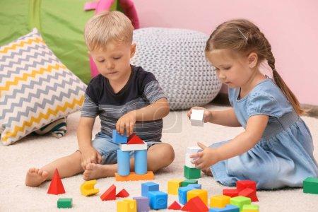 Foto de Niños lindos jugando con constructor en planta en casa - Imagen libre de derechos