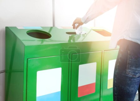 Woman throwing paper into litter bin outdoors. Recycling concept